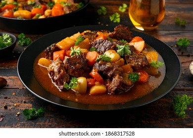 Beef Stew with carrot and baby potato in black plate on wooden table