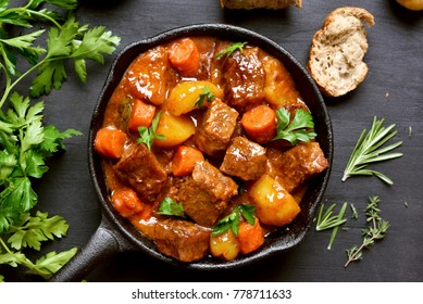 Beef stew, goulash in cast iron pan. Top view, flay lay