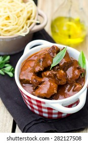Beef stew goulash with gravy served with pasta. Selective focus