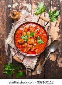 beef stew or goulash in old pan served with spoon and napkin on rustic wooden background, top view