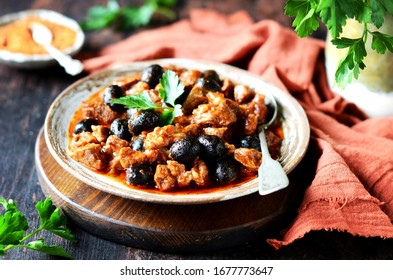 Beef stew with olives and tomatoes on a dark background, rustic