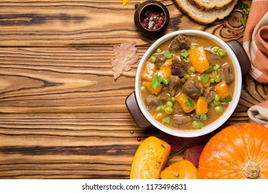 Beef stew with pumpkin, peas and thick sauce, autumn tasty food. Dark bowl on wooden background in rustic style