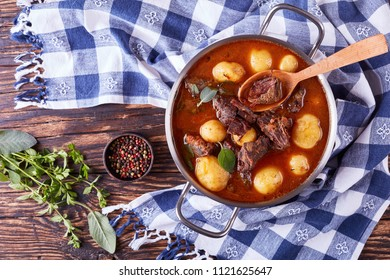 Beef Stew with tender cubes of meat, whole new potatoes, carrots and herbs in a metal casserole on old rustic wooden table with kitchen towel, irish cuisine, view from above, close-up