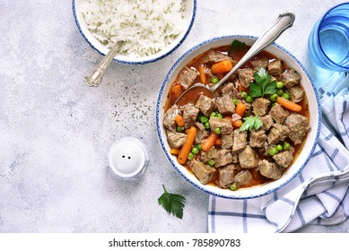 Beef stew with vegetables garnished with boiled rice in a vintage bowl over light slate, stone or concrete background.Top view.