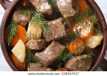beef stew with vegetables and herbs in a pot macro. background horizontal view from the top.