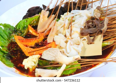 Beef string winter melon string enoki mushroom edible tree fungus lettuce rice cake beef omasum red hot soup in white porcelain bowl isolated on white background
