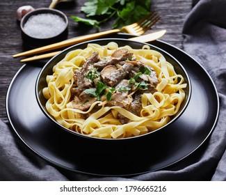 boeuf stroganoff cuit à la sauce champignons aigre-crème, servi avec des nouilles d'oeuf dans un bol noir à la fourchette dorée et au couteau sur une table en bois foncé, en gros plan, vue sur le paysage