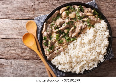 beef stroganoff and rice close-up on a plate on the table. horizontal view from above