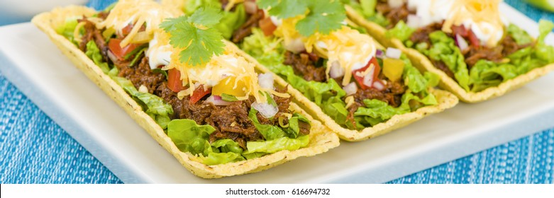Beef Tacos - Shredded beef taco trays topped with salsa, sour cream and grated cheese.