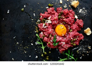 Beef tartare on a black slate or metal background- traditional dish of french cuisine.Top view.