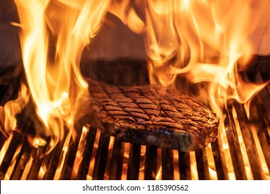 Beef T-bone steaks ( dallas steaks ) on the grill with flames.
