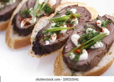 Beef tenderloin crostini with green on a plate