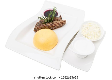 Beef tenderloin and a hominy with white cheese. This isolated ion a white background. Close-up.