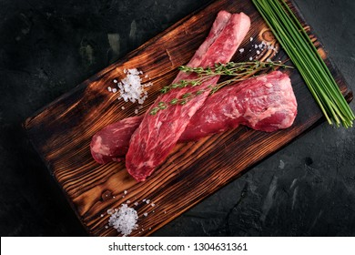 beef tenderloin on a wood Board with salt and thyme top view, skirt steak