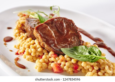 Beef Tenderloin with Ptitim or Birdy and Parmesan Cheese Isolated on White Background. Restaurant Main Course with Veal Meat, Israeli couscous, Brown Sause and Greens Close Up