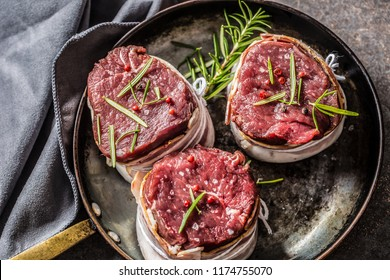 Beef tenderloin steaks wrapped in bacon stored into the pan.