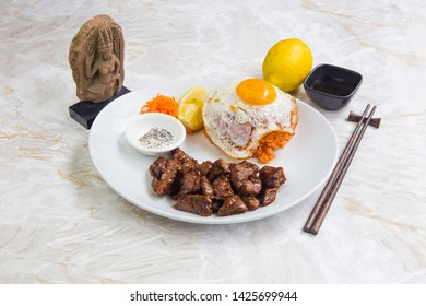 Beef thai food with omelette and rice, served with carrots and lemon on a white round plate. Dishes on a marble table.