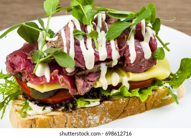 Beef veel sandwich, mayonnaise rocket garnish isolated on brown background