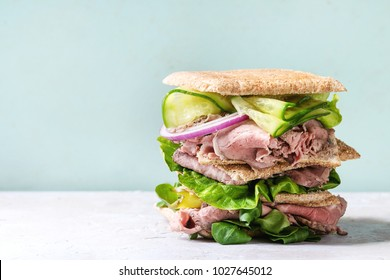 Beef and vegetables sandwiches with sliced meat, cucumber, green salad, rye whole grain bread in stack over grey green pin-up style background.