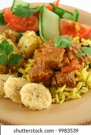 Beef vindaloo curry on tumeric rice with a side salad.