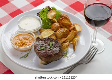 Beefsteak with home made potato fries two sauces, rosemary and glass of red wine