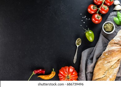 Beefsteak tomatoes, baguette and tomatoes selection over stone table. Top view with copy space. Mediterranean cuisine. Italian food concept