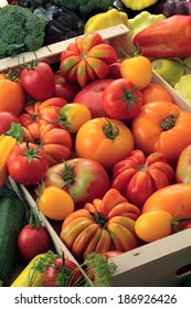 Beefsteak tomatoes, red and yellow tomatoes, broccoli,  zucchini, mallow, bell pepper and eggplants in a wooden box