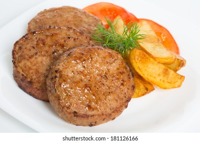 beefsteak in a white plate served with fried potato and tomatoes