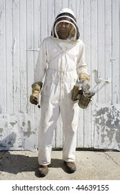 A beekeeper dressed in full protective clothing