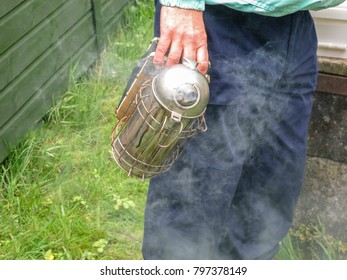 Beekeeper holding a smoking smoker before using it to open a beehive