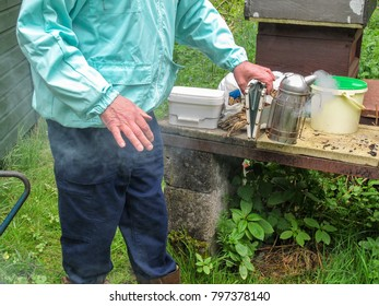 Beekeeper operating the bellows of a smoker