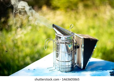 Beekeeper Smoker smokes white smoke. Apiary background. Beekeeping tool close up. Smoker stands on the ground on the green grass. Beekeeping apiary. Work at the apiary