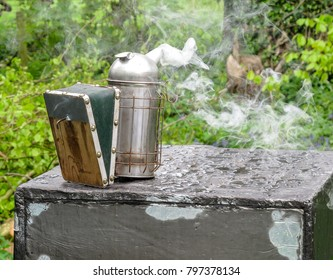 Beekeepers metal somker smoking on the top of a beehive.  The silver smoker has green bellows