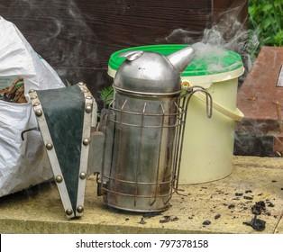 Beekeping smoker lits and smoking next to a pile of fule