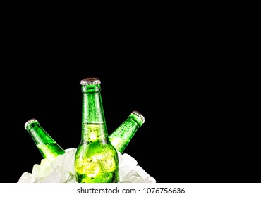 Beer, alcohol. Bottles of chilled alcohol in a pile of ice on a black background. Party, beach party. Copy space