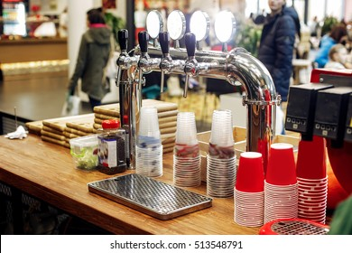 beer bar with stylish taps and plastic cups  on wooden desk. catering in food court at mall concept. space for text. modern kitchen