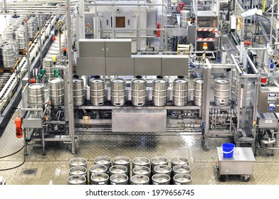 beer barrels in the filling process in a brewery - beer production in the modern food industry