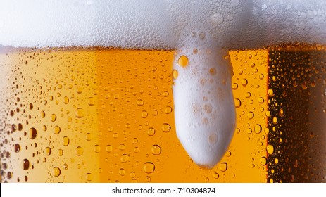 Beer being poured. Foam sliding down side of beer glass