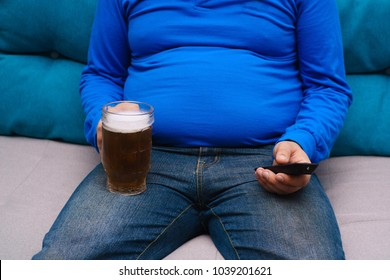 Beer belly, overweight. Man with obese abdomen sitting om the coach with tv remote and mug of beer, close up. Alcoholism, unhealthy, sedentary lifestyle