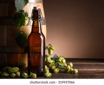 Beer bottle with beer barrel and fresh hops