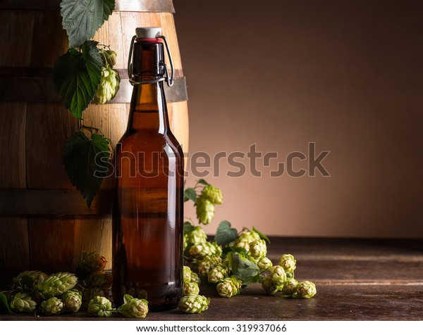 Beer bottle with beer barrel and fresh hops