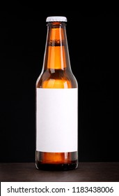 Beer bottle with blank label isolated on black background