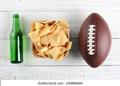 Beer bottle, bowl of chips and an American style football on a rustic whitewashed wood surface. Horizontal format. The bottle is without label.