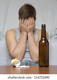 Beer bottle and drugs on the table. Depressed and lonely man.