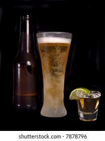 Beer bottle, frosty glass of beer and a shot of tequila