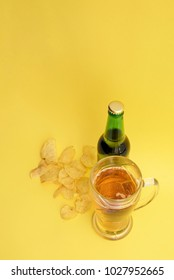 Beer bottle, glass mug with beer and chips on a yellow background