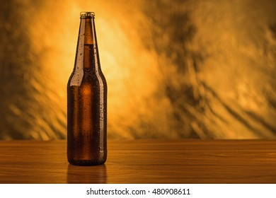Beer bottle isolated on gold background