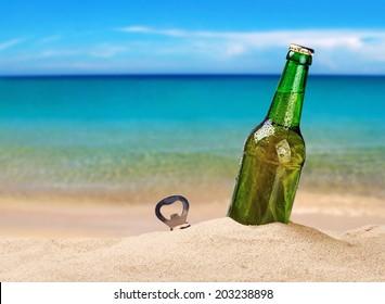 Beer bottle on a sandy beach with clear sky