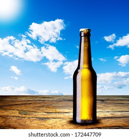Beer bottle on wood table and summer scene background
