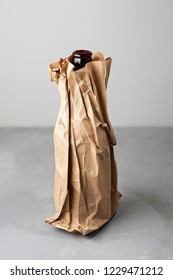Beer bottle in the paper bag on gray concrete background. Close up view with copy space